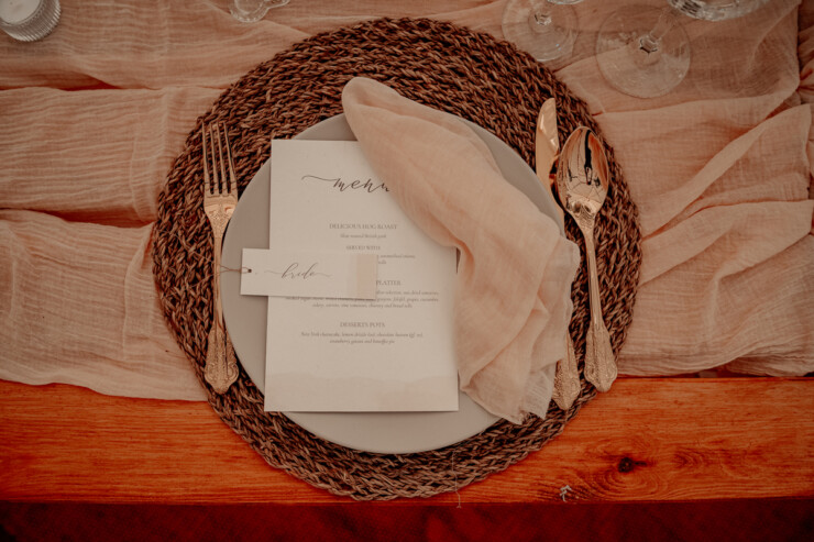 Wedding menu made of tree free cotton recycled paper, positioned on a grey plate with a raffia place mat. Boho vintage style wedding in a tipi